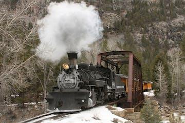 historic train riding through colorado landscape