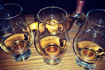 a glass of scotch on a table