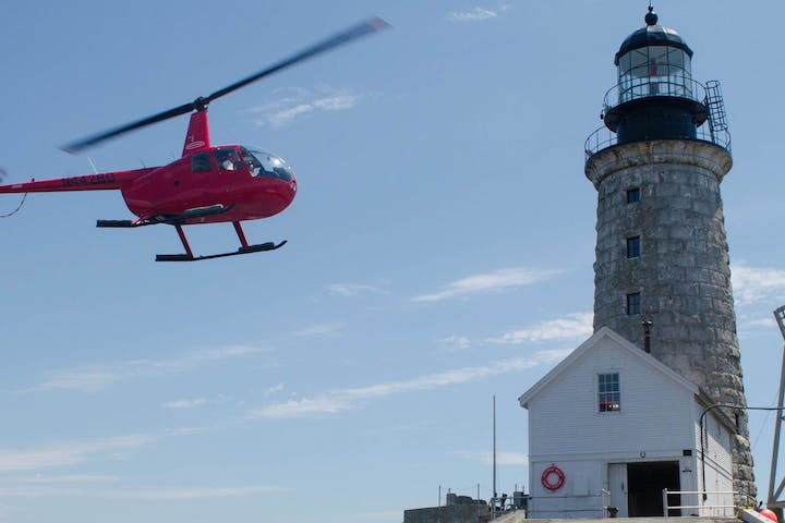 seacoast helicopter flying by lighthouse