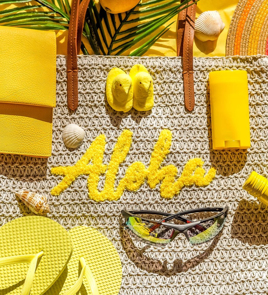 yellow-flatlay-of-beach-items-like-aloha-tote-suns-WBM6HUDAQ