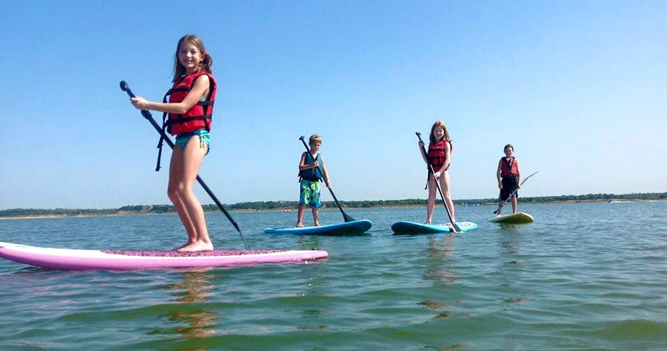 A group of kids enjoy Junior Stand Up Paddleboarding (SUP) Camp with LBI Surfing.