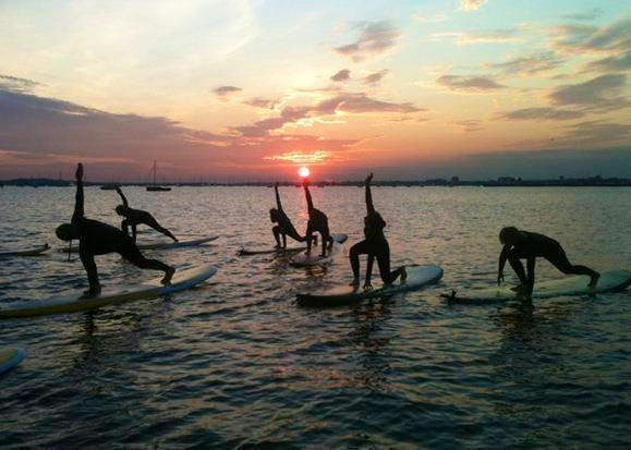 A group practices SUP yoga on the water with LBI Surfing.