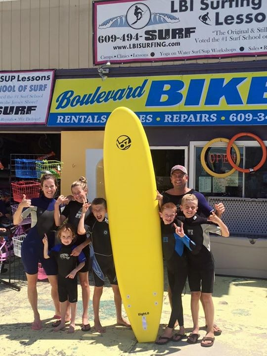 A family poses with a surfboard in front of LBI Surfing.