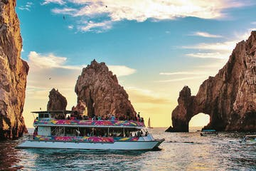 a small boat in a body of water with Arch of Cabo San Lucas in the background