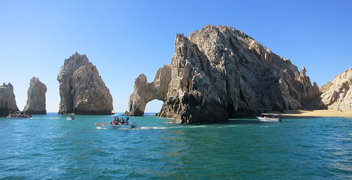 a group of people on a rock near the ocean with Arch of Cabo San Lucas in the background