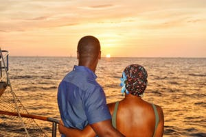 a couple standing on a boat next to a body of water