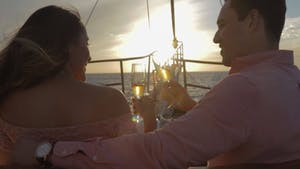 a couple toasting with a wine glass on a boat during sunset
