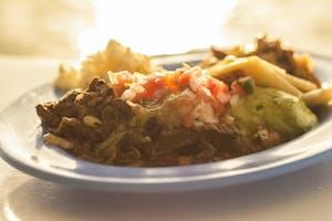 A dish of meat fajitas with guacamole