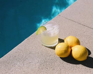 a glass with liquor by a pool