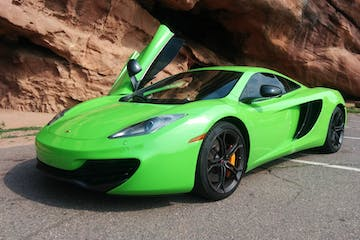 Green McLaren in a parking lot.