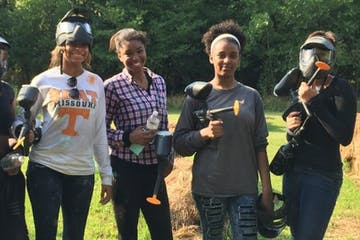 a group of women playing paintball
