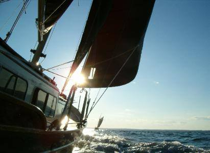 The sun gleams against the Pineapple Ketch as it sails in the open ocean