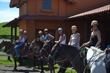 a group of people riding horses tour