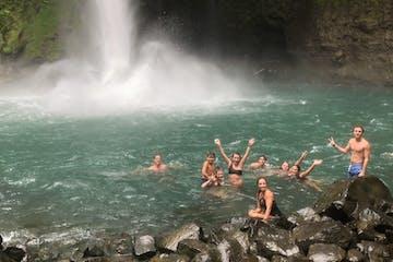 People swimming at La Fortuna Waterfall in Arenal