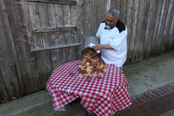 A chef pouring a feast onto a table.
