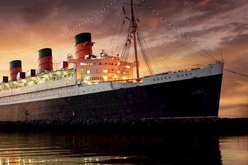 a large ship in a body of water with RMS Queen Mary in the background