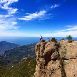 A person posed on the edge of a cliff in Malibu