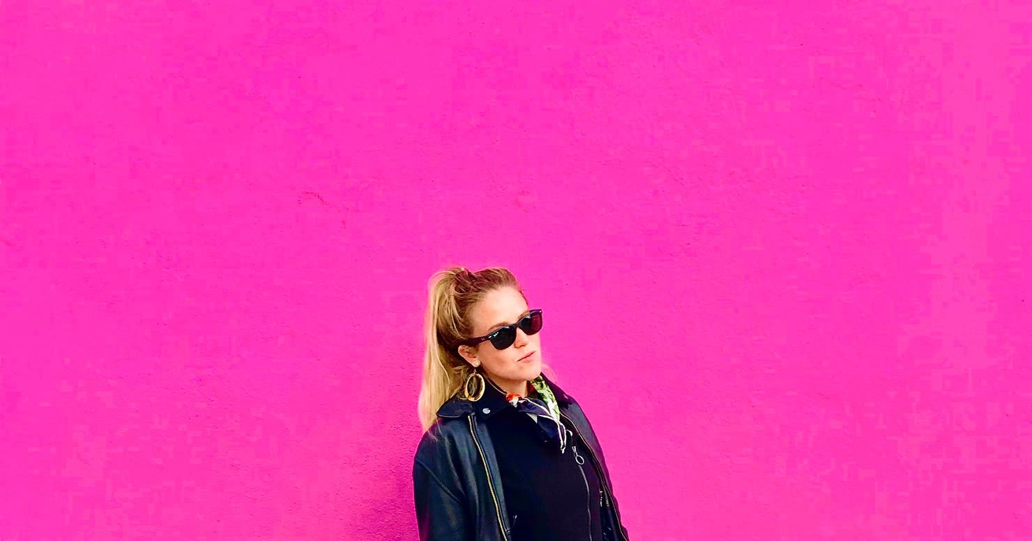 Girl in front of pink wall