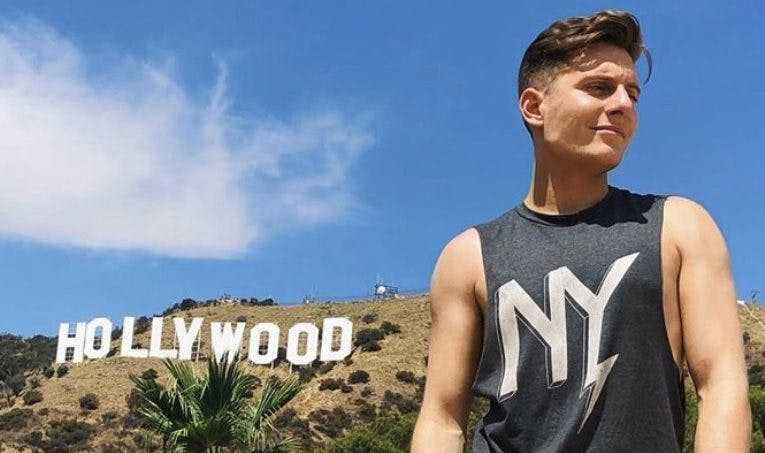 young man standing under the hollywood sign