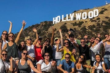 a group of people beneath the hollywood sign
