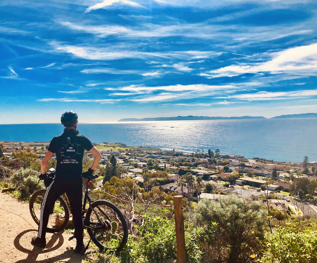 a guide from bikes and hikes la standing next to the pacific ocean