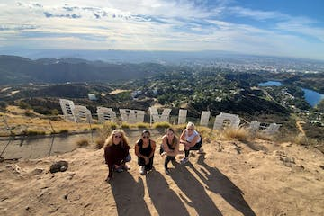 four girls hike behind the hollywood sign