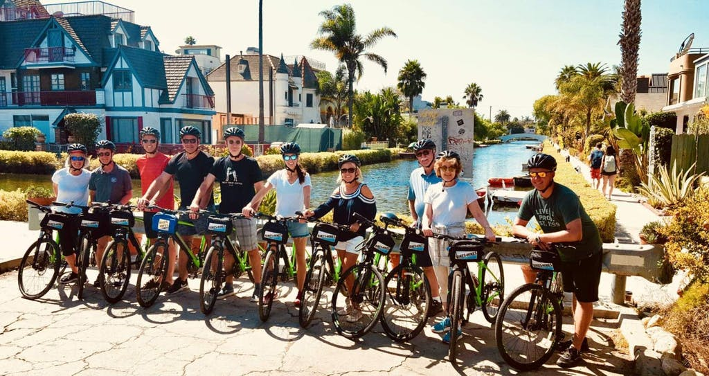a group of people and bicycles on a bike tour of the venice canals