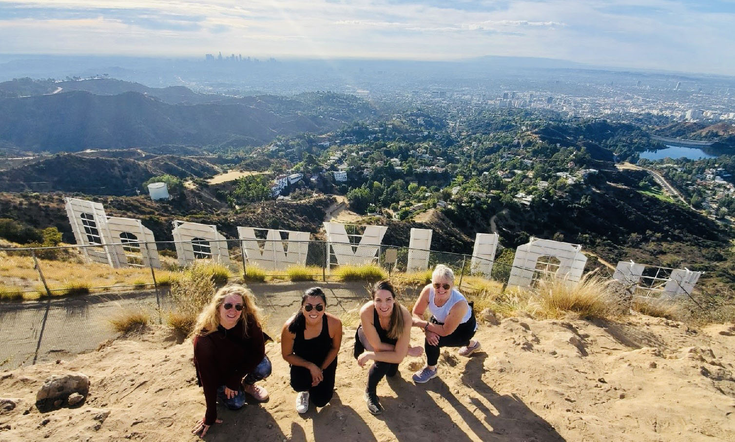 four people hiking behind the hollywood sign