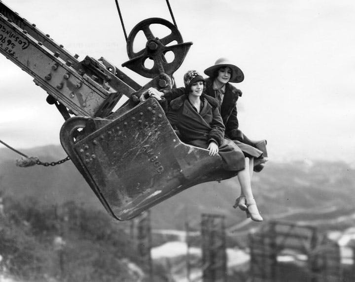 two women being lifted into the air by the hollywood sign