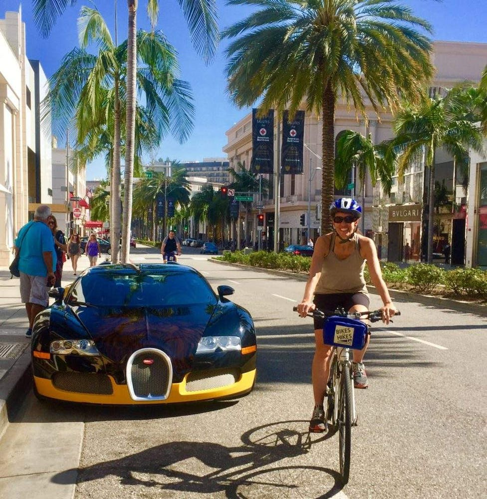 a group of people riding bikes down a street next to a palm tree