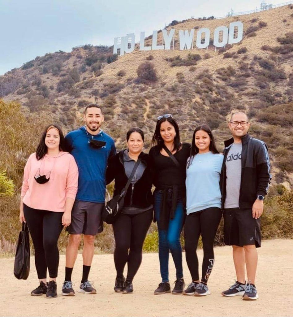 a group of people posing for a photo below the hollywood sign