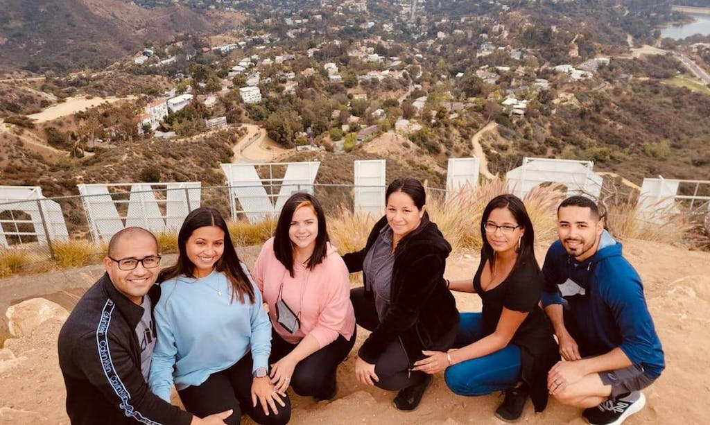 a group of people posing on a hike behind the hollywood sign
