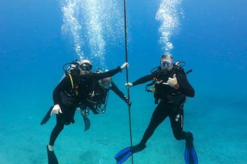 Two scuba divers underwater on Oahu, Hawaii