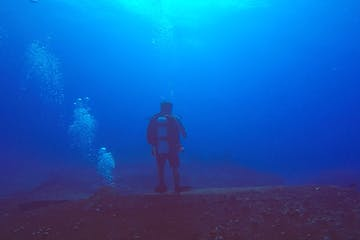 Scuba diver standing on underwater wreck in Oahu, Hawaii