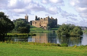 a castle on top of a lush green field with Ripley Castle in the background