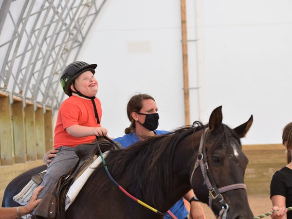 boy participating in equine therapy