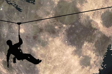 Silhouette of a zip liner in front of a bright moon