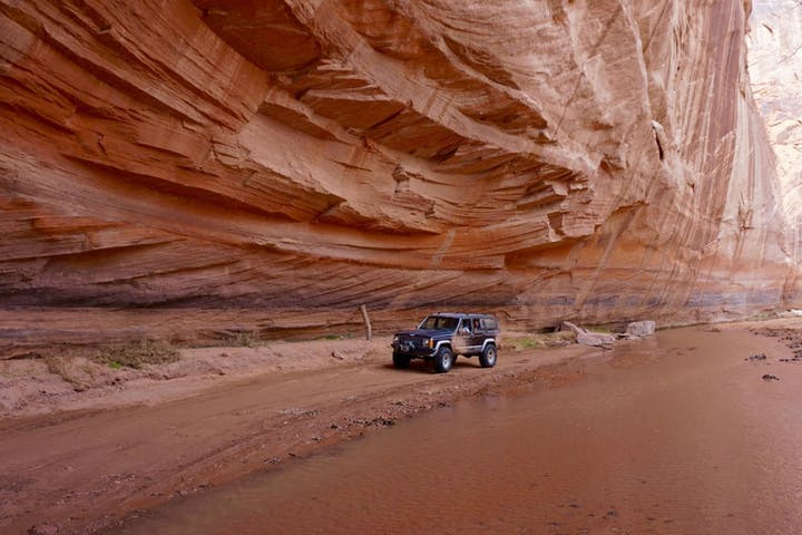 A Jeep next to the flooding canyon floor and under a tilting canyon wall