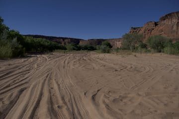 The sandy canyon floor covered in car and horse tracks