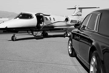 Black and white photo of a private jet and a chauffeur vehicle.