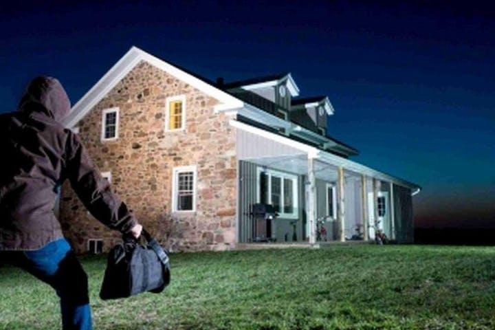 burglar approaching huge house in the dark