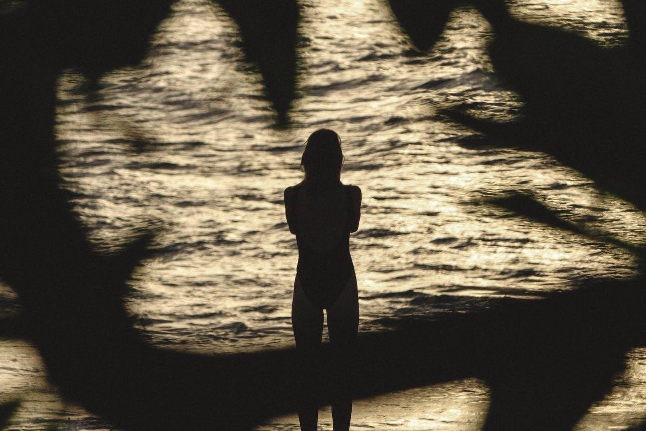 Woman from behind staring at a lake