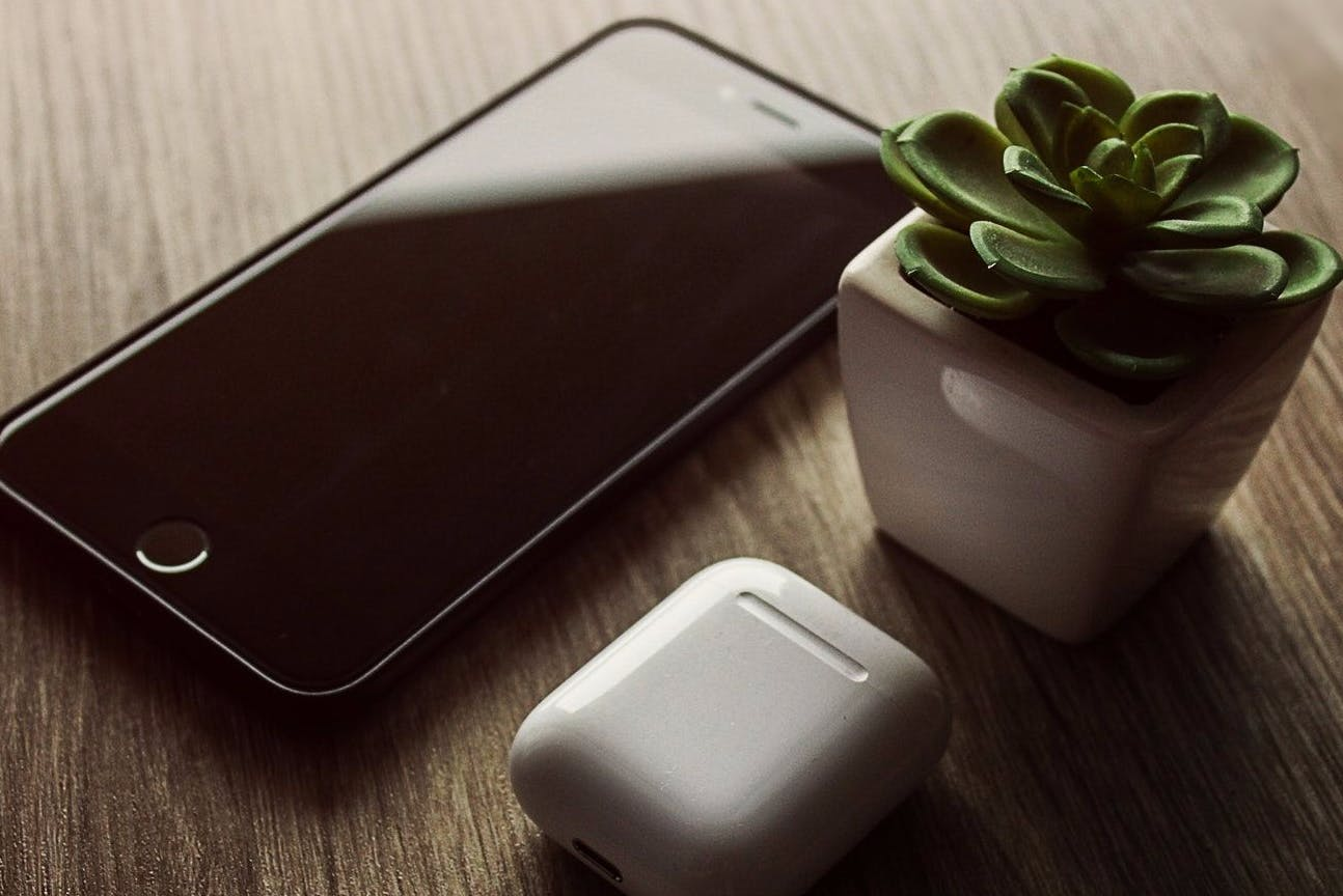 Cellphone on a wooden table next to a dessert plant and charger