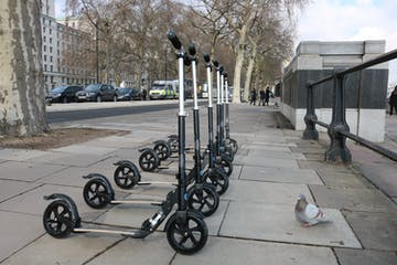 Electric Scooters on London Sidewalk with Pigeon
