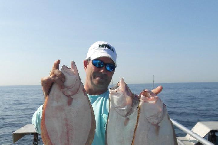 A fisher with three fluke fish