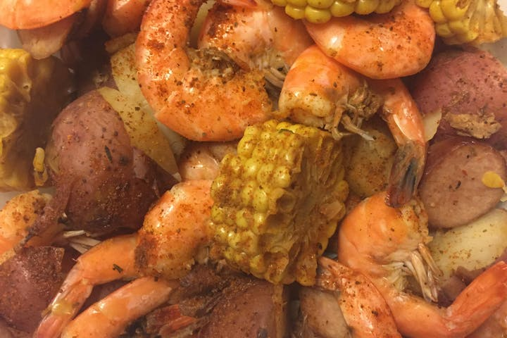 Seafood, corn, and potatoes in a pot.