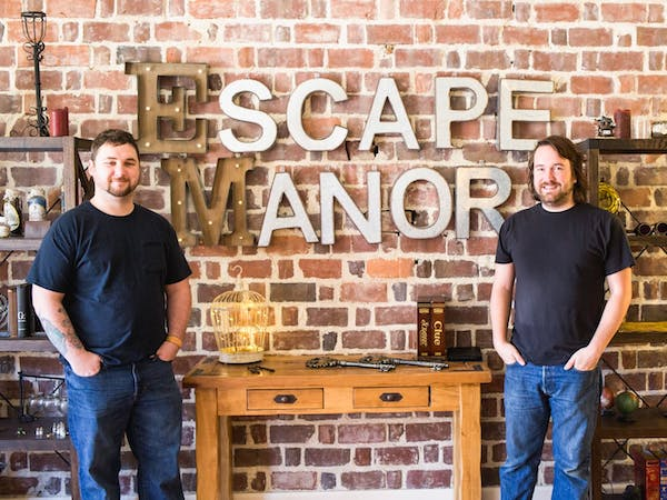 two men standing in front of Escape Manor sign