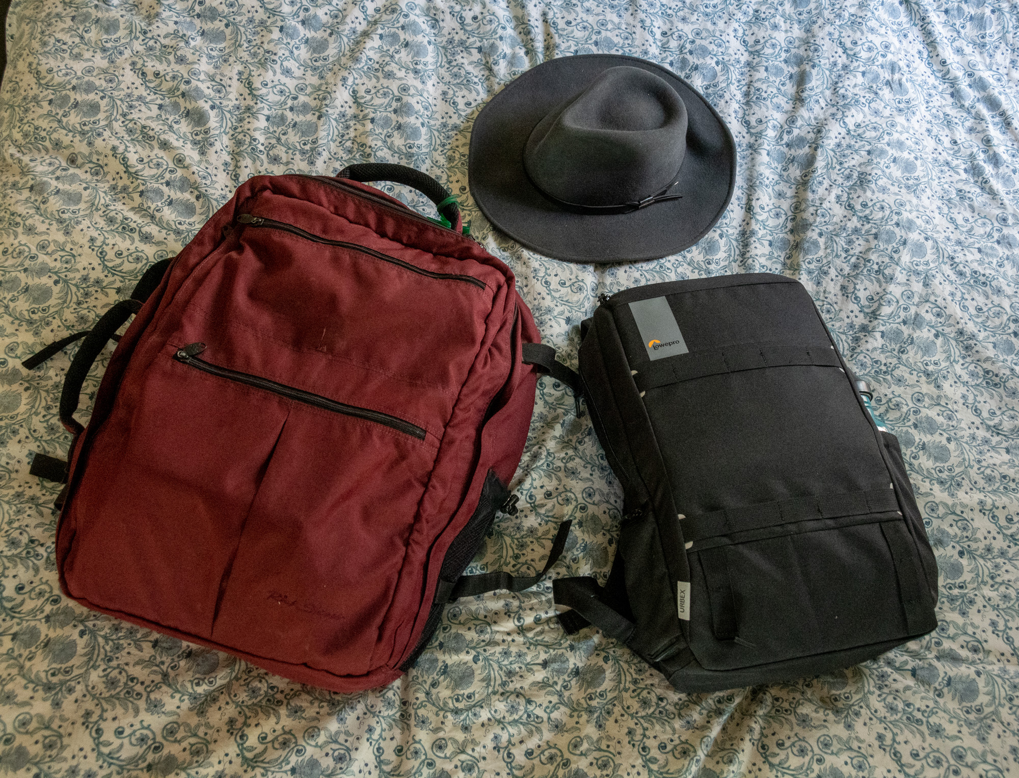 2 pieces of luggage and a hat, packed and ready to travel