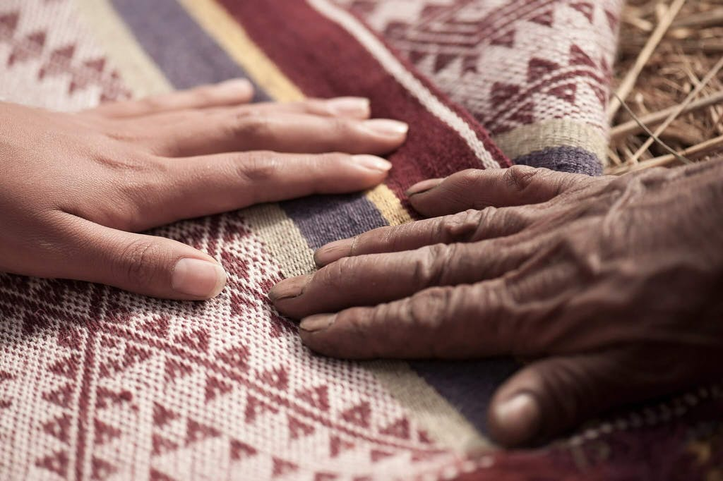 Hands touching woven cloth