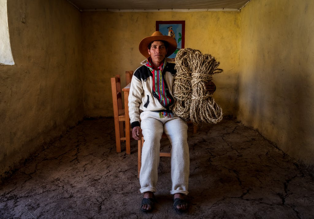 man sitting with woven grass used to build the last Incan bridge